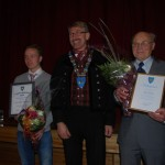 Idrettsprisen til Jostein og kulturprisen til Eldor, her sammen med prisutdeler ordfører Kåre Helland